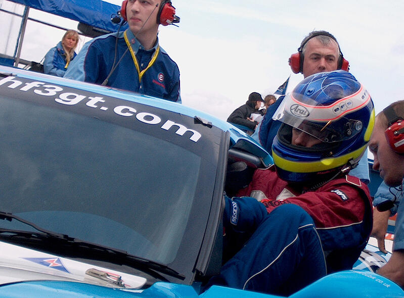 Race Car Driver Getting into Car with Pit Crew Wearing Headsets Around Them